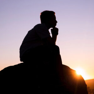 Person in thinking pose at dawn
